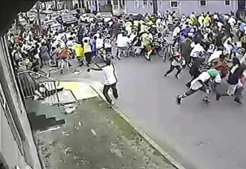 FILE - In this file photo image taken from video and provided May 13, 2013 by the New Orleans Police Department, a possible shooting suspect in a white shirt, bottom center, shoots into a crowd of people during a Mothers Day, Parade in New Orleans. Gunfire one bozy Mardi Gras weekend, a mass shooting at a jazz music parade and the gunshot deaths of three children in 2013 nearly overshadowed a promising statistic New Orleans Mayor Mitch Landrieu touts as he seeks re-election Saturday: the city's murder rate dropped last year by nearly 20 percent. Still, the violence stubbornly continues and crime is a major election issue as Landrieu seeks four more years. Though many voters say they still don't feel safe, local pundits say Landrieu is positioned to beat two fellow Democrats, with a runoff date of March 15 if needed. (AP Photo/New Orleans Police Department, File)