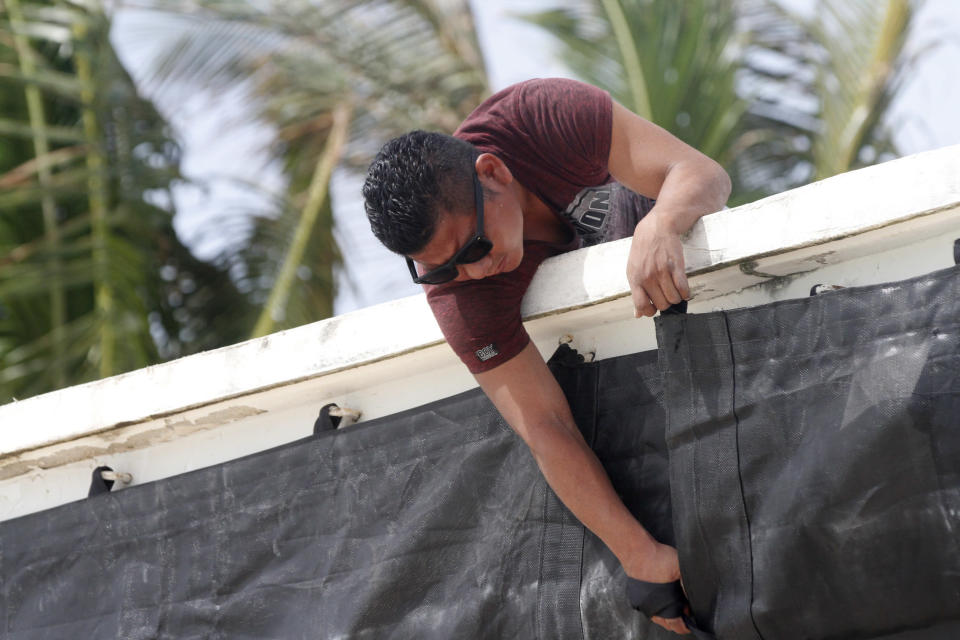 A worker installs a tarpaulin at the entrance of a beach club in preparation for the arrival of Tropical Storm Zeta in Playa del Carmen, Mexico, Monday, Oct. 26, 2020. A strengthening Tropical Storm Zeta is expected to become a hurricane Monday as it heads toward the eastern end of Mexico's resort-dotted Yucatan Peninsula and then likely move on for a possible landfall on the central U.S. Gulf Coast at midweek. (AP Photo/Tomas Stargardter)