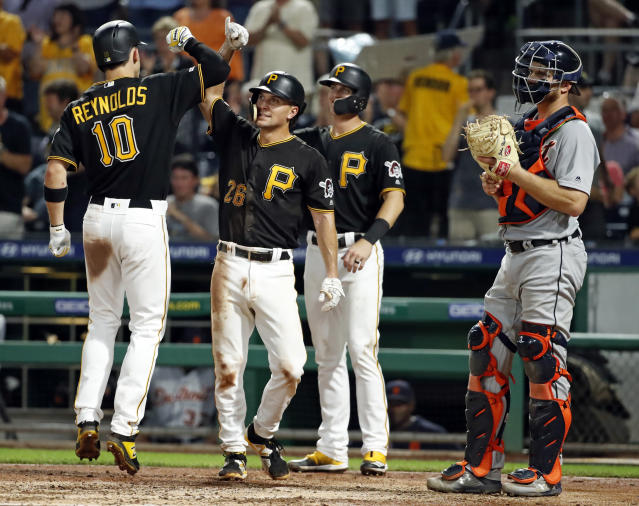 Pittsburgh Pirates' Bryan Reynolds (10) celebrates with Adam Frazier (26) and Kevin Newman after hitting a three-run home run off Detroit Tigers relief pitcher Nick Ramirez during the sixth inning of a baseball game in Pittsburgh, Wednesday, June 19, 2019. (AP Photo/Gene J. Puskar)