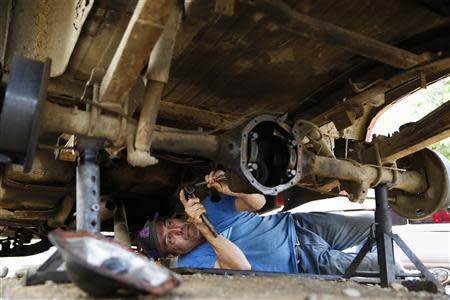 Auto mechanic Juan Freire works under a vehicle in his home at El Chaparral neighbourhood in La Guaira May 2, 2014. REUTERS/Carlos Garcia Rawlins