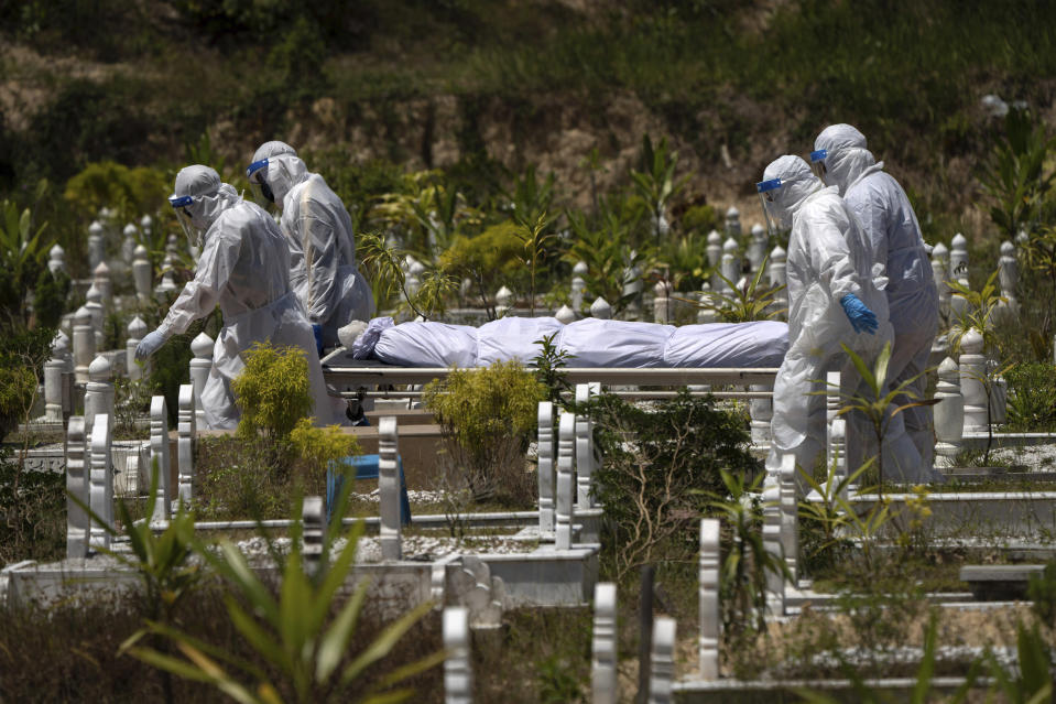 In this Feb. 5, 2021, file photo, workers wearing personal protective equipment (PPE) carry the body of a victim of the coronavirus disease at a Muslim cemetery in Gombak on the outskirts of Kuala Lumpur, Malaysia. Images of bodies burning in open-air pyres during the peak of the pandemic in India horrified the world in May, but in the last two weeks Malaysia and two other Southeast Asian nations have surpassed India's peak per capita death rate as a new coronavirus wave tightens its grip on the region. (AP Photo/Vincent Thian, File)