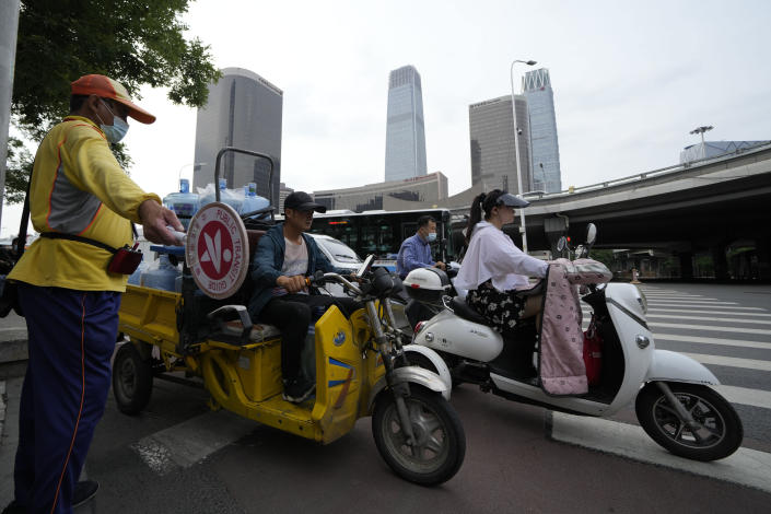 """A traffic warden guides commuters pasting through the Central Business District during rush hour in Beijing on Friday, July 2, 2021. A small but visible handful of urban Chinese are rattling the ruling Communist Party by choosing to """"lie flat,"""" or reject high-status careers, long work hours and expensive cities for a """"low-desire life."""" That clashes with party ambitions to make China a wealthier consumer society. (AP Photo/Ng Han Guan)"""