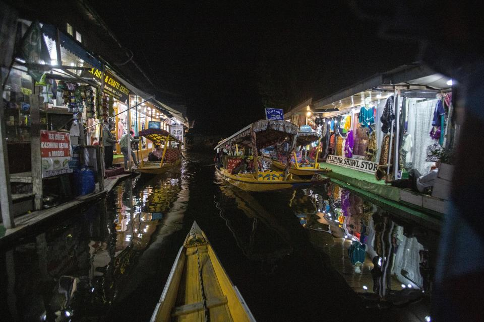 A Kashmiri boatman rows his boat carrying Indian tourists at a market in the interior of Dal Lake in Srinagar, Indian controlled Kashmir on Aug. 2, 2021. Tourists are returning to the valleys and mountains in Indian-controlled Kashmir, as infections in the Himalayan region and nationwide come down after a deadly second wave earlier this year. (AP Photo/Mukhtar Khan)