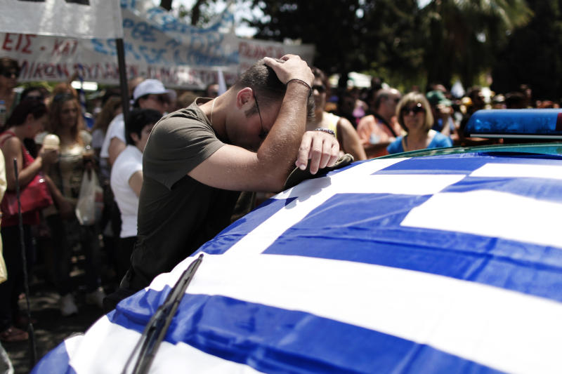 A striking Municipal police officer reacts as he leans on a car with a Greek flag during a protest, against new austerity cuts that will affect thousands of public sector workers, in Athens, Friday, July 12, 2013. The measures are part of a broad plan to slash the size of Greece's bloated public sector, which counts some 670,000 employees. The government has committed to firing 15,000 people by the end of 2014 and transferring another 12,500 to new positions this year. (AP Photo/Petros Giannakouris)