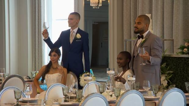 Two couples pose for a photo at a wedding venue behind a dining table. Halifax-based Simply Weddings staged a photo shoot on Monday. (CBC - image credit)