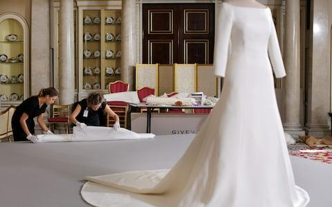 Conservator from the Royal Collection carefully unwrap the veil of Megan Duchess of Sussex's wedding dress  - Credit: ITV Pictures