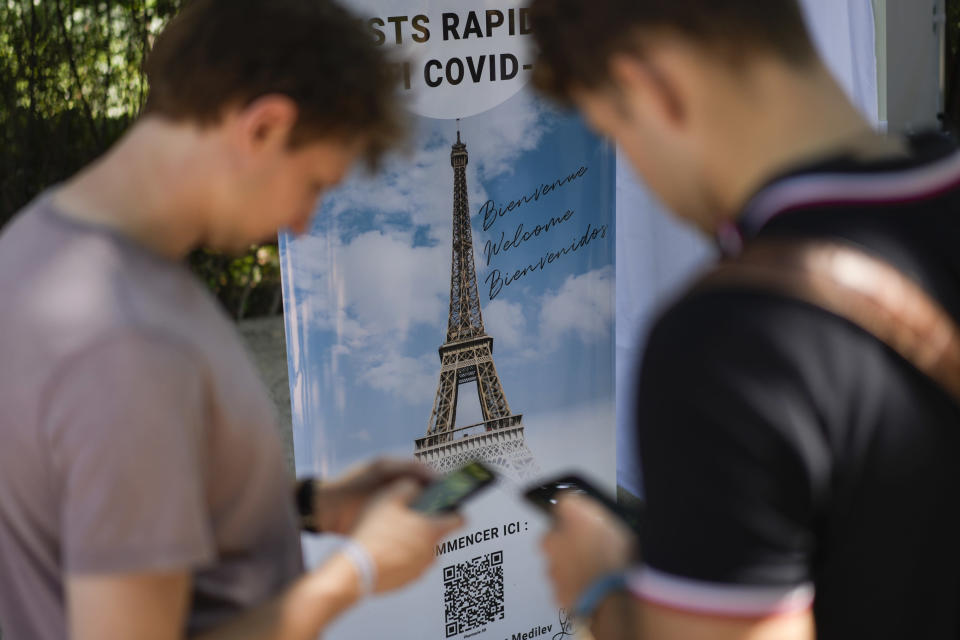 FILE - In this Wednesday, July 21, 2021 file photo, visitors register for COVID-19 tests at the Eiffel Tower in Paris. For Europe's battered tourism industry, fresh virus outbreaks and chaos and confusion over travel rules are contributing to a another cruel summer. With COVID-19 variants surging in parts of Europe, popular destination countries are taking measures to contain outbreaks. In France, the world's most visited country, visitors to cultural and tourist sites were confronted Wednesday, July 21, 2021 with a new requirement for a special COVID-19 pass. To get it, people must prove they're either fully vaccinated or recently recovered from an infection, or produce a negative virus test. (AP Photo/Daniel Cole, File)
