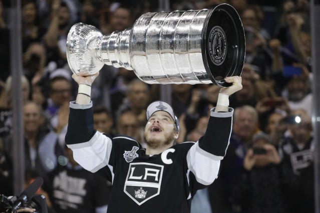 Los Angeles Kings right wing Dustin Brown raises the Stanley Cup after beating the New York Rangers in overtime in Game 5 of the NHL Stanley Cup Final series Friday, June 13, 2014, in Los Angeles. (AP Photo/Jae C. Hong)