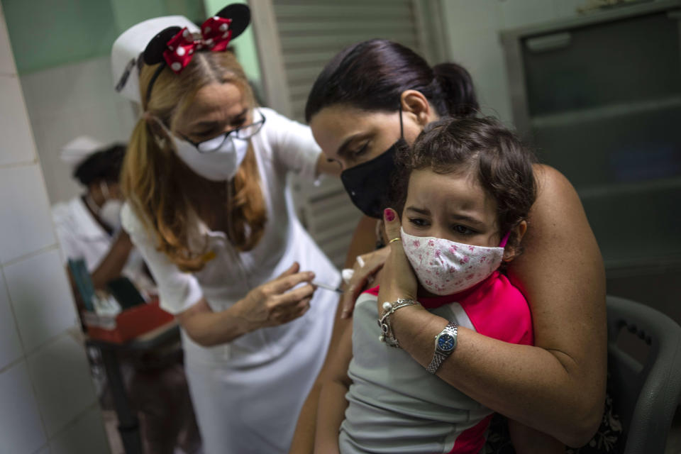 A mother holds her daughter who is injected with a dose of the Soberana-02 COVID-19 vaccine, in Havana, Cuba, Thursday, Sept. 16, 2021. Cuba began inoculating children as young as 2-years-old with locally developed vaccines on Thursday.(AP Photo/Ramon Espinosa)