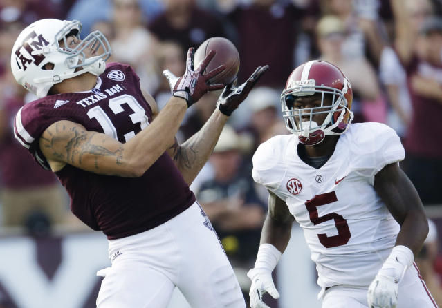 Texas A&M wide receiver Mike Evans (13) makes a 95-yard touchdown reception as Cyrus Jones (5) looks on during the fourth quarter of an NCAA college football game Saturday, Sept. 14, 2013, in College Station, Texas. (AP Photo/David J. Phillip)