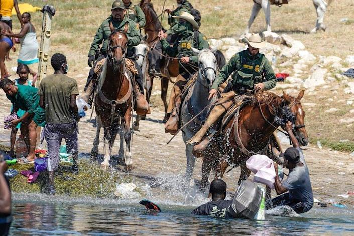 US Border Patrol agents on horseback tries to stop Haitian migrants from entering an encampment on the banks of the Rio Grande near the Acuna Del Rio International Bridge in Del Rio, Texas on September 19, 2021
