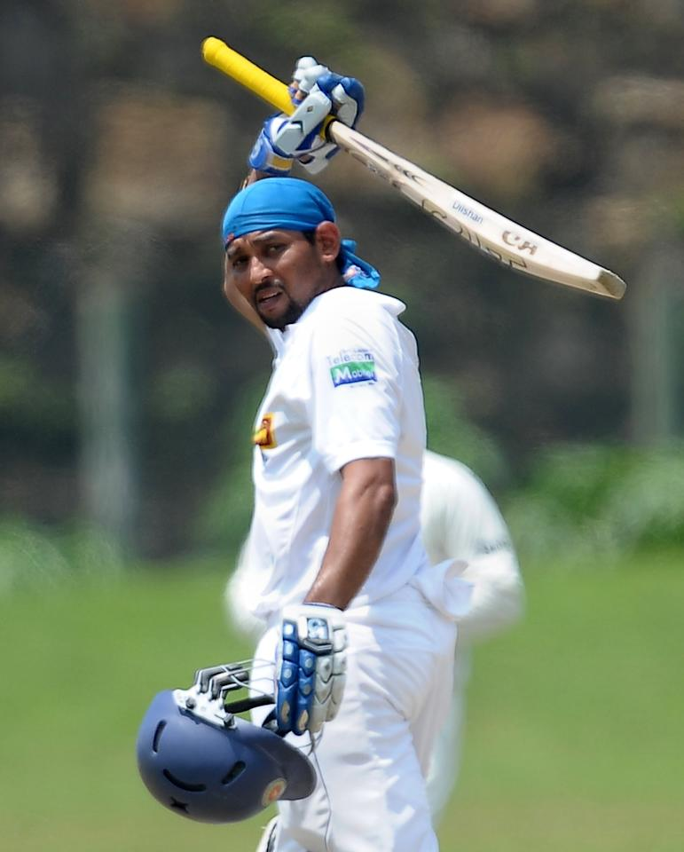 Sri Lankan batsman Tillakaratne Dilshan raises his bat after he scored a century (100 runs) during the final day of the opening Test match between Sri Lanka and Bangladesh at the Galle International Cricket Stadium in Galle on March 12, 2013. AFP PHOTO/ LAKRUWAN WANNIARACHCHI        (Photo credit should read LAKRUWAN WANNIARACHCHI/AFP/Getty Images)