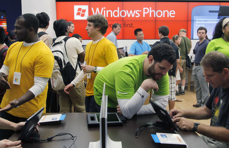 Product Advisor Alex Kennedy, of Boston, center right, assists a costumer at the opening of a new Microsoft store inside the Prudential Center mall, in Boston, Thursday, Aug. 23, 2012. Microsoft unveiled a new logo Thursday at three stores in Boston and the Seattle area. (AP Photo/Steven Senne)