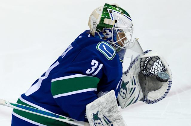 Vancouver Canucks' goalie Eddie Lack, of Sweden, makes a glove save against the Winnipeg Jets during the second period of an NHL hockey game in Vancouver, British Columbia, on Sunday, Dec. 22, 2013. (AP Photo/The Canadian Press, Darryl Dyck)