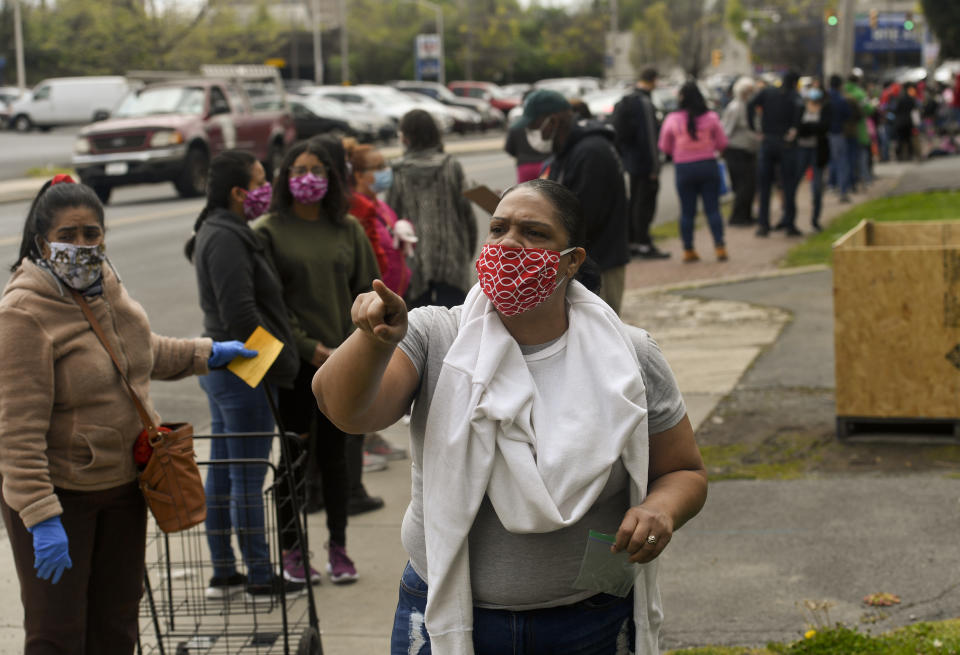 Volunteer Elizabeth Castro asks people in line to stand 6ft apart along Greenwich Street in Reading, PA on April 25, 2020. (Photo: Ben Hasty/MediaNews Group/Reading Eagle via Getty Images)