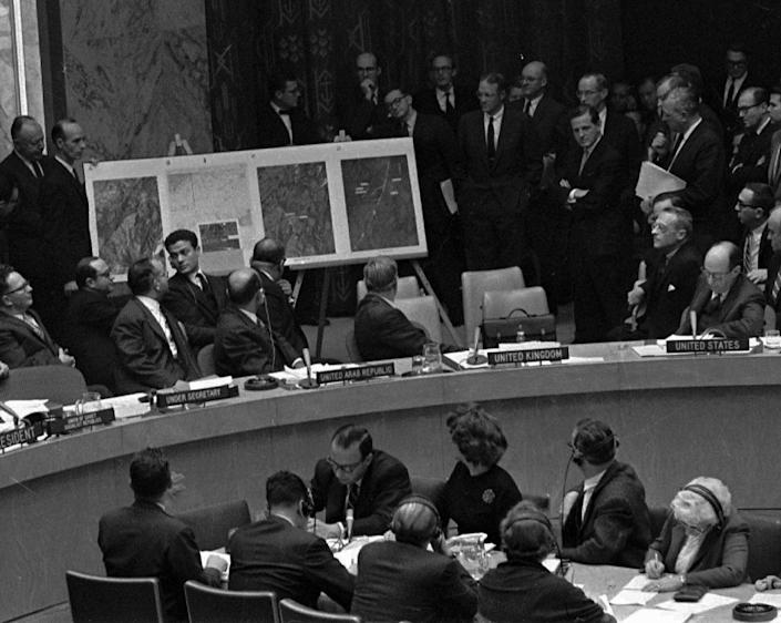 FILE - In this Oct. 25, 1962 file photo, U.S. Ambassador Adlai Stevenson, far right, describes aerial photographs of launching sites for intermediate range missiles in Cuba during an emergency session of the United Nations Security Council at U.N. Headquarters at the height of the Cuban Missile Crisis. Israeli Prime Minister Benjamin Netanyahu's use of a cartoon-like drawing of a bomb to convey a message over Iran's disputed nuclear program this week, follows in a long and storied tradition of leaders and diplomats using props to make their points at the United Nations. (AP Photo/Files)