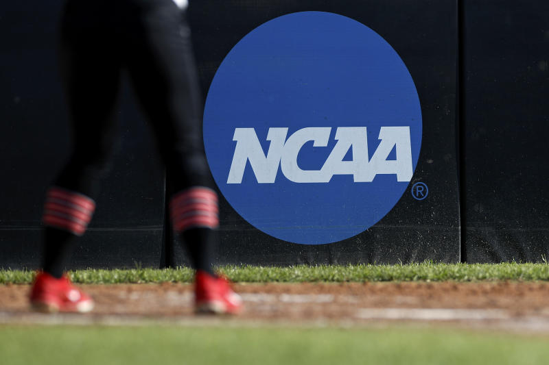FILE - In this April 19, 2019, file photo, an athlete stands near a NCAA logo during a softball game in Beaumont, Texas. California will let college athletes hire agents and make money from endorsements, defying the NCAA and setting up a likely legal challenge that could reshape U.S. amateur sports. (AP Photo/Aaron M. Sprecher, File)