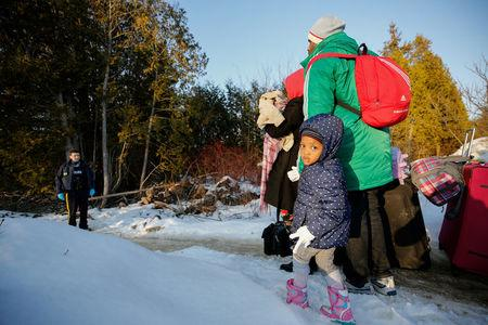 A girl waits with her family before crossing the US-Canada border into Canada in Champlain