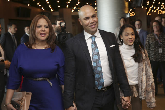 FILE - In this Nov. 4, 2019, file photo, New York Mets new manager Carlos Beltran arrives at an introductory baseball news conference with his family, including his wife Jessica Beltran, left, at Citi Field in New York. Beltran is out as manager of the Mets. The team announced the move Thursday, Jan. 16, 2020. (AP Photo/Seth Wenig, File)
