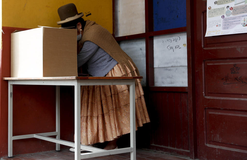 A woman stands at the voting booth during general elections in La Paz, Bolivia, Sunday, Oct. 18, 2020. (AP Photo/Juan Karita)