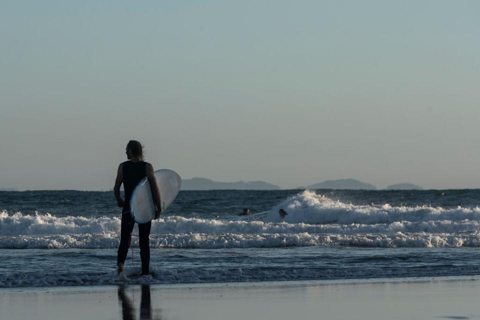 A surfer makes his way out to sea at The Pass in Byron Bay, Australia.