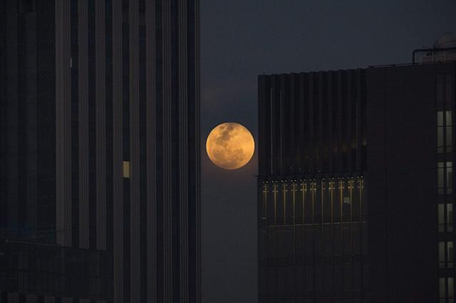 <p>The moon rises between two office buildings in Bangkok on Jan. 31, 2018. (Photo: Lillian Sunwanrumpha/AFP/Getty Images) </p>