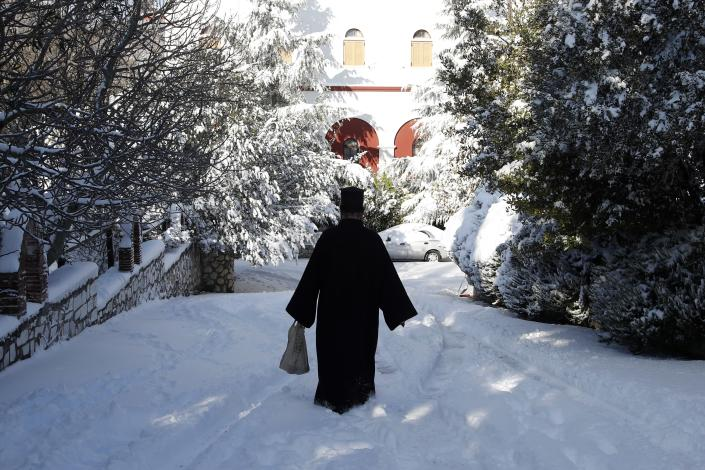 A Greek Orthodox priest walks at a snow-covered road at Penteli Monastery in northern Athens, Tuesday, Jan. 8, 2019. Schools will remain closed across many parts of the country as a new cold weather front brings freezing temperatures and heavy snowfall. (AP Photo/Thanassis Stavrakis)