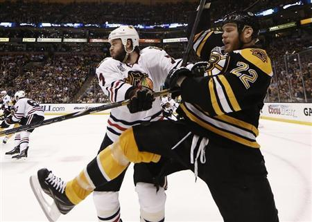 Boston Bruins right wing Shawn Thornton (22) is hit into the boards by Chicago Blackhawks defenseman Brent Seabrook (7) in Game 3 of their NHL Stanley Cup Finals hockey series in Boston, Massachusetts, June 17, 2013. REUTERS/Winslow Townson