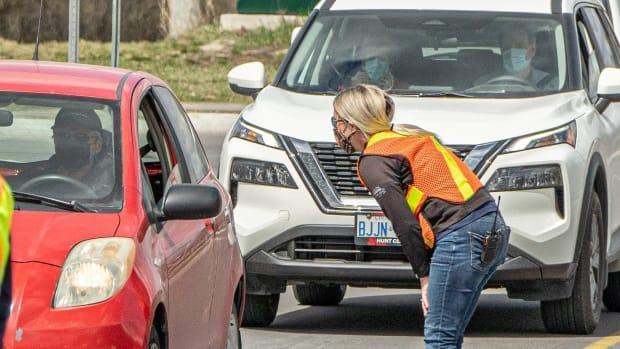 A worker directs people in their cars at the Nepean Sportsplex vaccination clinic in Ottawa on April 12. (Brian Morris/CBC - image credit)