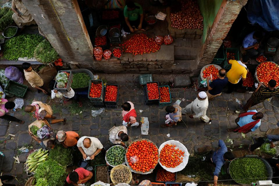 People shop at a crowded wholesale vegetable market in Delhi's old quarter after authorities eased coronavirus restrictions following a drop in infections (REUTERS)