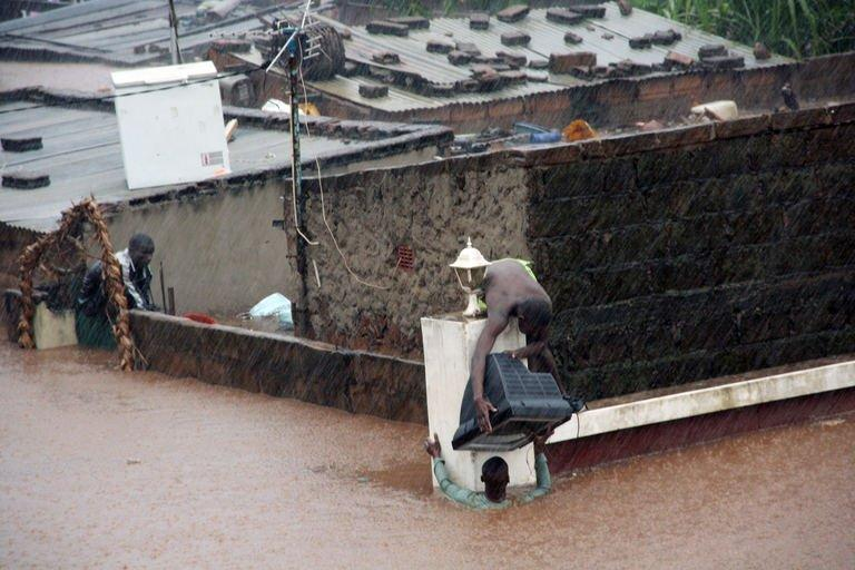 A resident of the Mozambican capital Maputo moves a TV set in the  heavy rain on January 15, 2013
