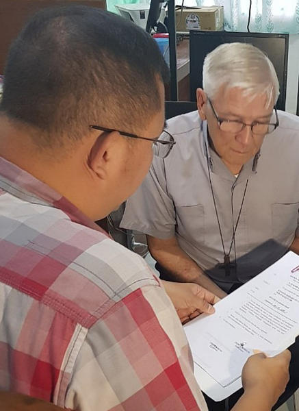 "In this Dec. 5, 2018, photo released by the Bureau of Immigration Public Information Office, American Roman Catholic priest Rev. Kenneth Bernard Hendricks, right, looks at documents after being arrested in a church in Naval town in the island province of Biliran, central Philippines. Philippine immigration authorities say they have arrested Hendricks accused of sexually assaulting altar boys in a remote central town in a case one official described as ""shocking and appalling."" (Bureau of Immigration PIO via AP)"