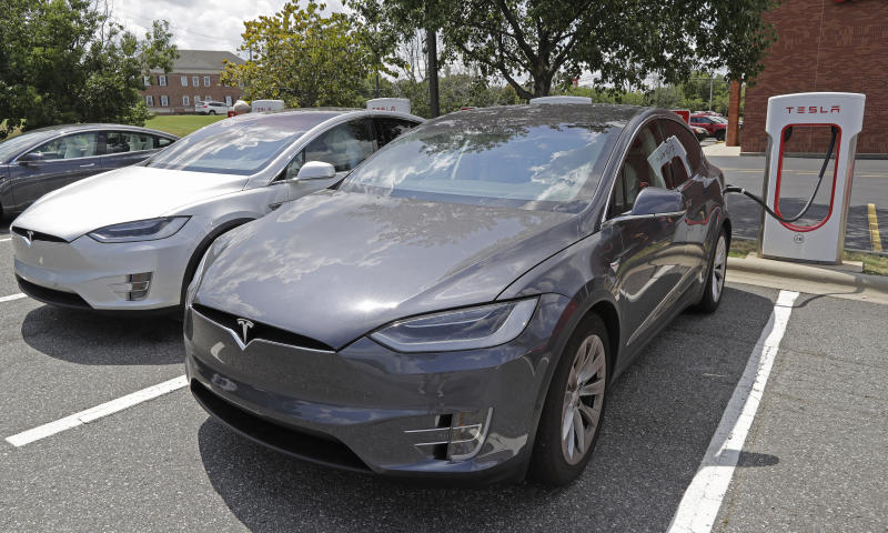 In this July 19, 2019, photo people wait inside their Tesla vehicles at a Tesla Supercharger site in Charlotte, N.C. Tesla, Inc. reports earning on Wednesday, July 24, 2019. (AP Photo/Chuck Burton)