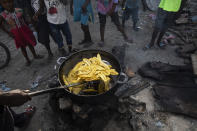 A vendor fries a batch of plantains at a market in the La Saline neighborhood near the main port entrance, partially burned by a gang two years ago, in Port-au-Prince, Haiti, Monday, Sept. 13, 2021. There could be as many as 100 gangs in Port-au-Prince; no one has an exact count and allegiances often are violently fluid. (AP Photo/Rodrigo Abd)