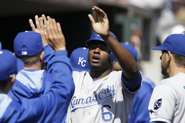 Kansas City Royals' Lorenzo Cain is congratulated after scoring during the fourth inning of a baseball game against the Detroit Tigers in Detroit, Monday, March 31, 2014. (AP Photo/Carlos Osorio)