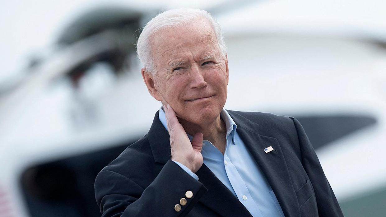 President Biden wipes his neck after a cicada landed on him before boarding Air Force One at Joint Base Andrews Wednesday. (Photo by Brendan Smialowski/AFP via Getty Images)