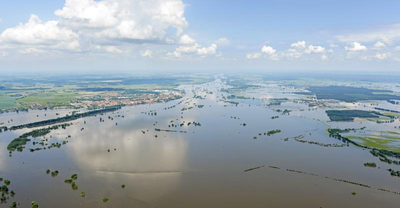 Clouds reflect in the floods by river Elbe near Tangermuende, left, central Germany, Tuesday, June 11, 2013. Weeks of heavy rain this spring have sent the Elbe, the Danube and other rivers such as the Vltava and the Saale overflowing their banks, causing extensive damage in central and southern Germany, the Czech Republic, Austria, Slovakia and Hungary. (AP Photo/Jens Meyer)