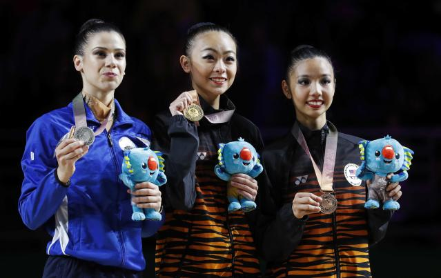Rhythmic Gymnastics - Gold Coast 2018 Commonwealth Games - Individual Ribbon Final - Coomera Indoor Sports Centre - Gold Coast, Australia - April 13, 2018. Gold medallist Kwan Dict Weng of Malaysia, silver medallist Diamanto Evripidou of Cyprus and bronze medallist Koi Sie Yan of Malaysia pose with their medals. REUTERS/David Gray