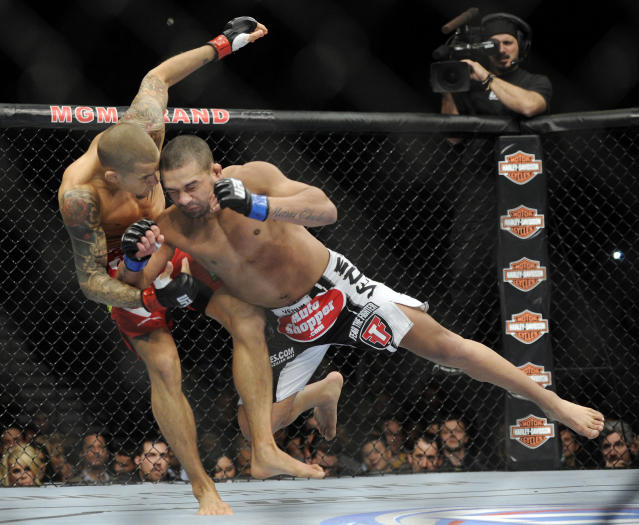 Diego Brandao, right, of Brazil, lunges at Dustin Poirier of Coconut Creek, Fla., during a UFC 168 mixed martial arts featherweight bout on Saturday, Dec. 28, 2013, in Las Vegas. Poirier won by a technical knockout in the first round. (AP Photo/David Becker)