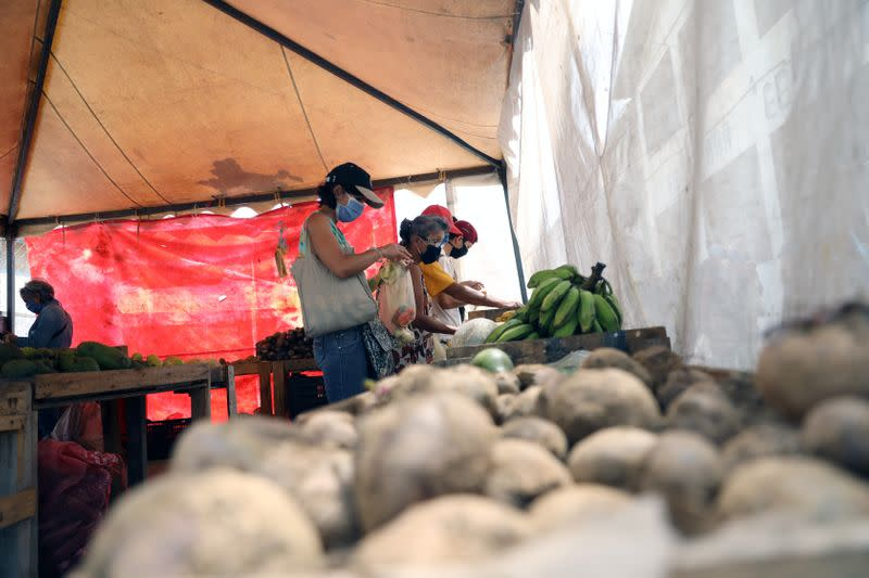 People wearing protective masks is seen shopping at a vegetables street market during the nationwide quarantine as coronavirus disease (COVID-19) continues in Caracas