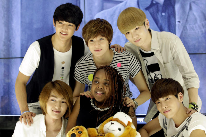 Donika Sterling from New York, center, poses for the media with members of South Korean pop group SHINee during their meeting in Seoul, South Korea, Wednesday, June 20, 2012. The 15 year-old American K-pop fan, who is suffering a disease that gradually causes loss of muscle tissue and slows down parts of the body, met and sang with the boy band she idolizes. (AP Photo/Lee Jin-man)