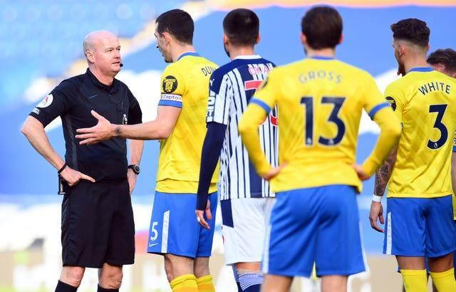 Referee Lee Mason (left) was left to explain to Brighton's Lewis Dunk why he had disallowed his free-kick.