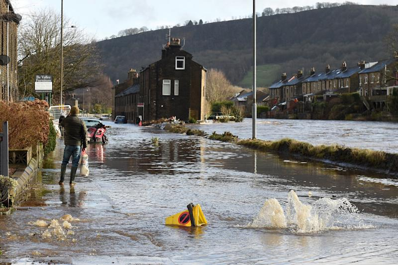 <strong>A man walks along a flooded street in Mytholmroyd, northern England, on February 9, 2020, after the River Calder burst its banks.</strong> (Photo: OLI SCARFF via Getty Images)