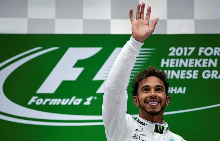 Mercedes' British driver Lewis Hamilton celebrates on the podium after winning the Formula One Chinese Grand Prix, in Shanghai, on April 9, 2017