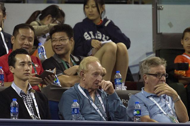 Tennis legend Rod Laver, center, bites his thumb as he watches a match between Italy's Fabio Fognini and Serbia's Novak Djokovic at the Shanghai Masters tennis tournament at the Qizhong Forest Sports City Tennis Center in Shanghai, China, Thursday, Oct. 10, 2013. Djokovic won 6-3, 6-3. (AP Photo/Ng Han Guan)