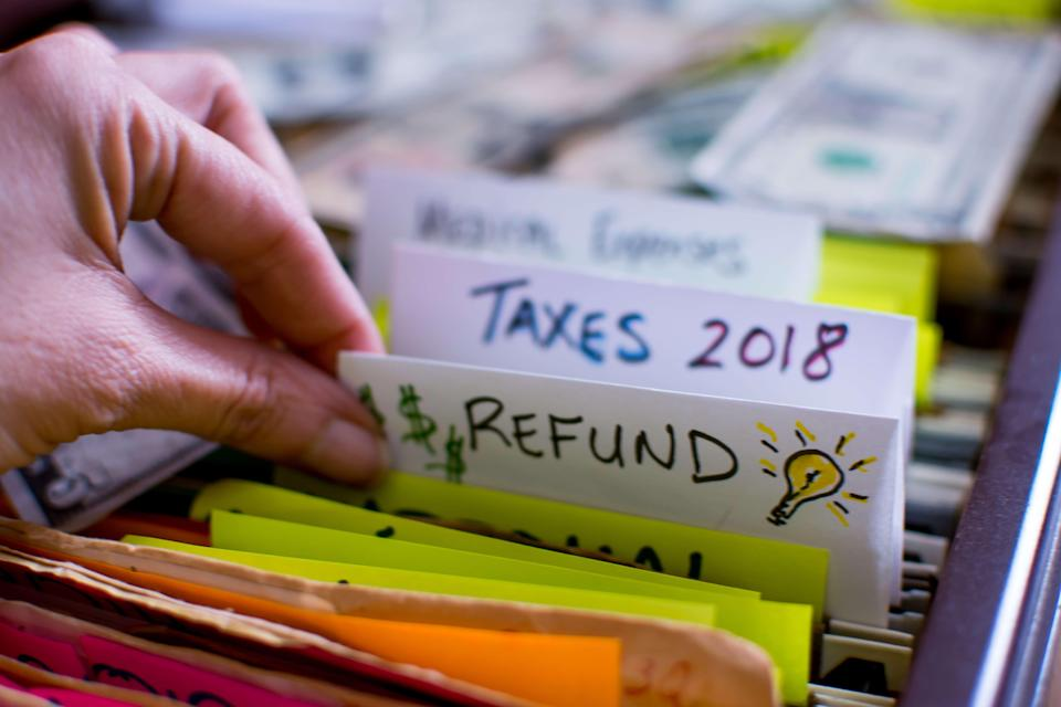 Hand pulling out file in filing cabinet with tax forms and papers with words Refund and Taxes 2018 handwritten on file folder conceptual dollar signs images and light bulb for ideas on tax refund conceptual financial planning photography.