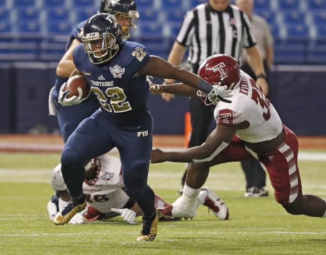 "FIU running back Shawndarrius Phillips (22) carries as Temple linebacker <a class=""link rapid-noclick-resp"" href=""/ncaaf/players/270005/"" data-ylk=""slk:William Kwenkeu"">William Kwenkeu</a> (35) reaches for him during the Gasparilla Bowl NCAA college football game Thursday, Dec. 21, 2017, in St. Petersburg, Fla. (Al Diaz/Miami Herald via AP)"