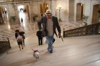 """Frida, a female Chihuahua (L), and owner Dean Clark walk up a flight of stairs in City Hall before the San Francisco Board of Supervisors issues a special commendation naming Frida """"Mayor of San Francisco for a Day"""" in San Francisco, California November 18, 2014. REUTERS/Stephen Lam"""