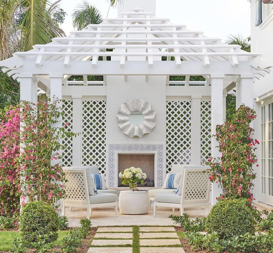 """<p>We simply can't get enough of Palm Beach-based designer <a href=""""http://www.phoebehoward.net/"""" rel=""""nofollow noopener"""" target=""""_blank"""" data-ylk=""""slk:Phoebe Howard"""" class=""""link rapid-noclick-resp"""">Phoebe Howard</a>'s ingenious use of this stunning pergola to connect a guest bedroom to the outdoor living space in a second home for a pair of Midwestern snowbirds. </p><p>This pergola is a gardener's dream, with plenty of trellises to grow your favorite blooms. And we adore this tiled fireplace for staying toasty during the mild South Florida winters. Who needs the beach when you have this elegant outdoor oasis?</p>"""