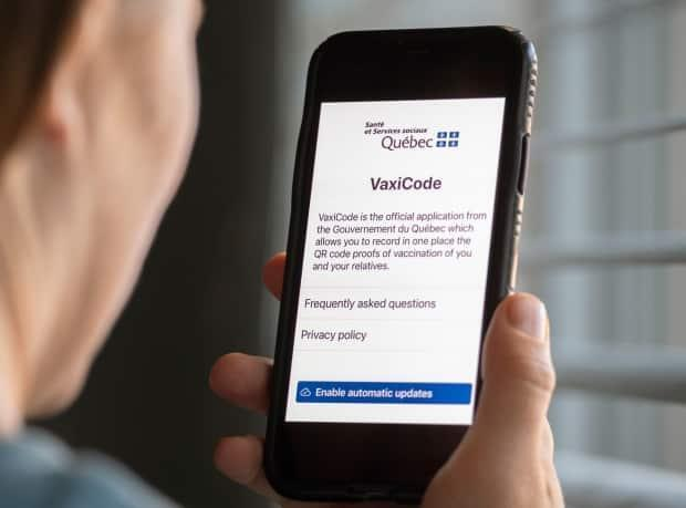 A woman looks at the Quebec government's new vaccine passport called VaxiCode on a phone in Montreal, Wednesday, August 25, 2021, as the COVID-19 pandemic continues in Canada and around the world.  (Graham Hughes/The Canadian Press - image credit)